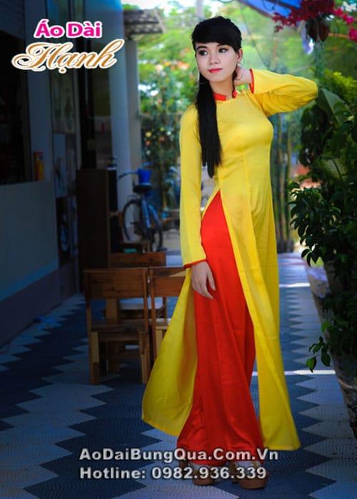 Áo dài vàng tươi lụa trơn cổ vuông hở viền đỏ tay dài